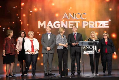 ANCC Magnet Recognition Program Leadership on stage with Magnet Prize recipient