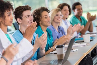 Diverse group of medical students applaud professor