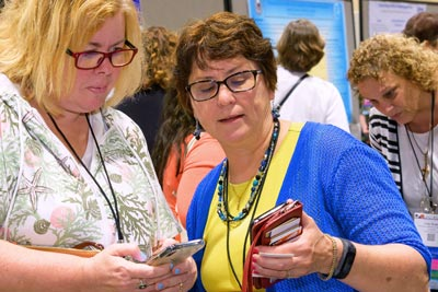 two nurses exchanging phone numbers at ANA Quality and Innovation Conference
